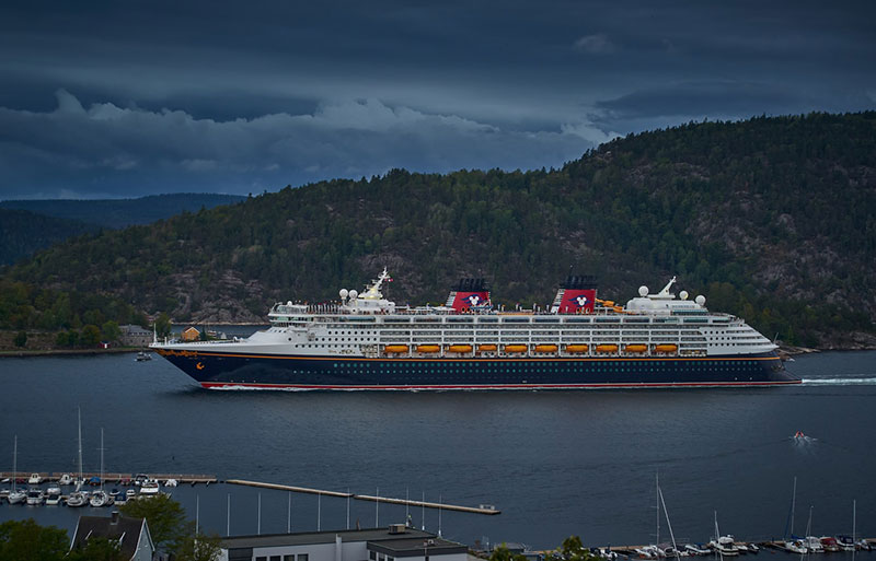 Disney Cruise sailing by island with storm clouds