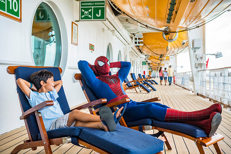 Spiderman and a kid relax on the Disney Magic at Disney Cruise Marvel Day at Sea