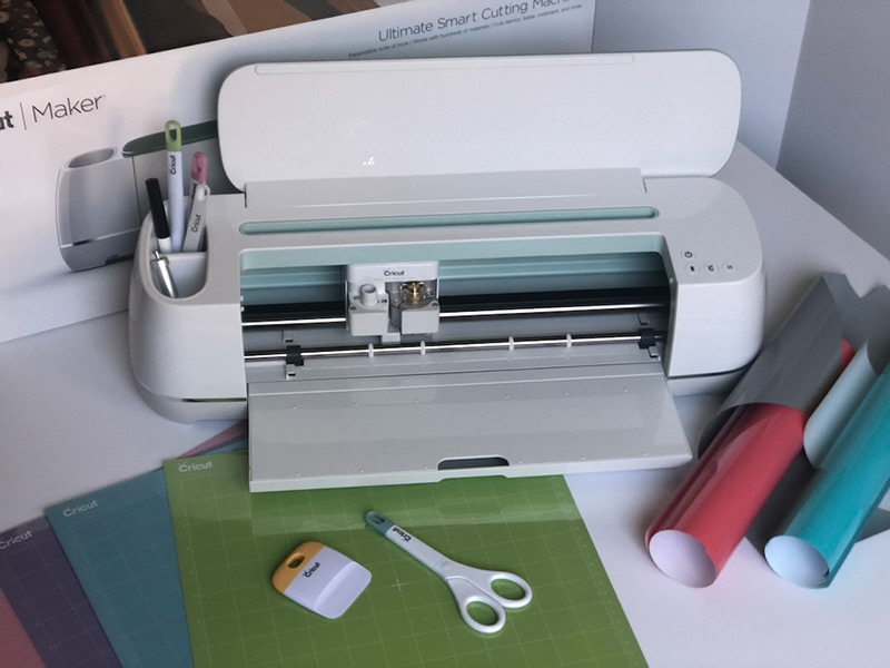 A Cricut Maker with paper and tools