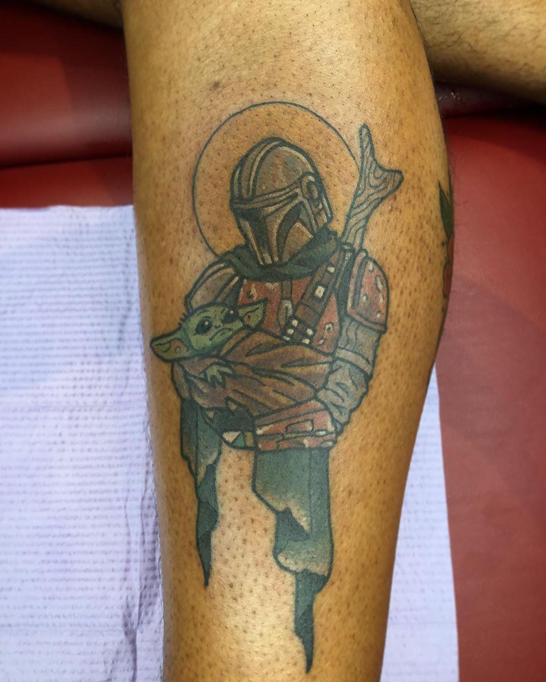 Mandalorian holding baby Yoda tattoo