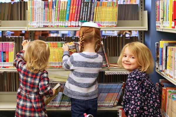 A group of children looking at a book shelf.