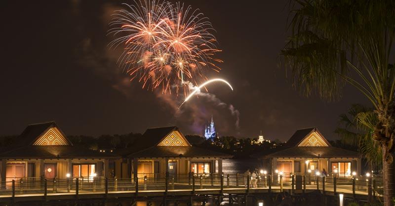 Polynesian Village Resort bungalows under fireworks over Disney World's Magic Kingdom